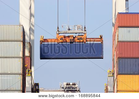 Sea container loaded onto a ship with a gantry crane in the Port of Rotterdam.