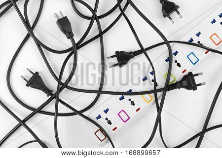 Messy of electrical cords plugs and wires unconnected electrical power strip or extension block with messy wires top view on white background messy electric equipment flat lay concept.