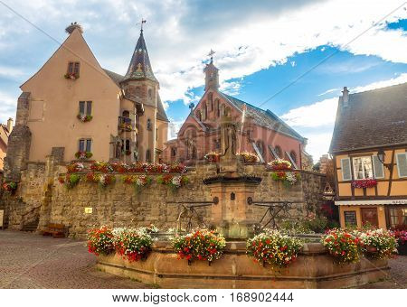 Beautiful view of square of Saint-Leon in the historic town Eguisheim, a popular tourist destination along the famous Alsace Wine Route, in beautiful evening light at sunset in summer, Alsace-Champagne-Ardenne-Lorraine, France