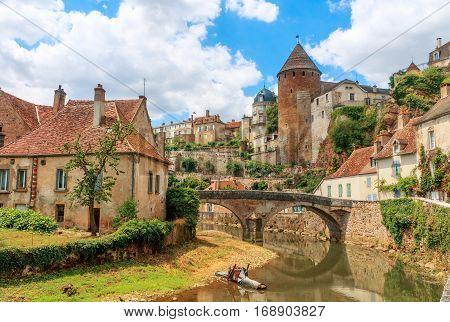 Quaint river through the medieval town of Semur en Auxois Burgundy France