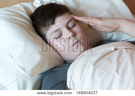 A boy with a headache lying in bed