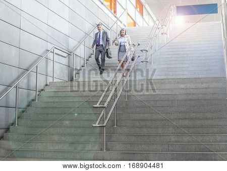 Businesspeople walking down stairs in train station