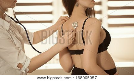 Friendly Female Medicine Doctor Holding Stethoscope And Listening To Pregnant Woman Standing For Enc