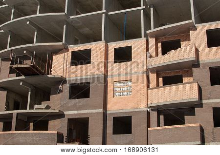 Multi-storey high-rise concrete and brick construction close-up