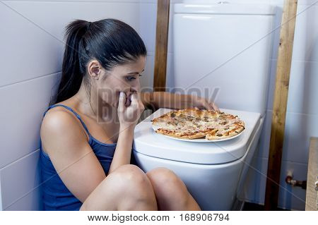 young sad and depressed bulimic woman feeling sick guilty sitting at the floor of the toilet leaning on WC eating pizza in nutrition disorder bulimia concept