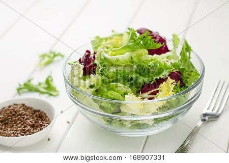Fresh Mixed Salad In Glass Bowl With Flax-seed On White Wooden Table.
