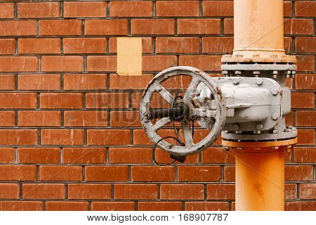 Gas valve on yellow natural gas distribution industrial pipe in front of red brick wall with copyspace vintage color-look