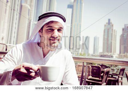 young arabian man having a cup of coffee at dubai marina
