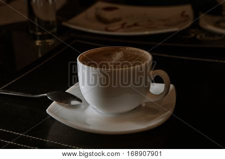 Side view of cappuccino cup on table in dark cafe room vintage color-look