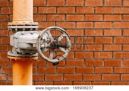 Natural gas distribution system valve in front of orange brick wall with place for text vintage color-look