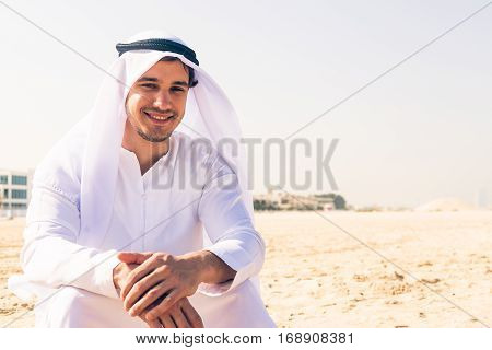 young arabian man sitting at the beach