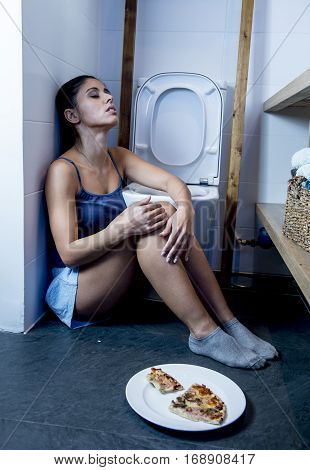 young sad and depressed bulimic woman feeling sick guilty after vomiting and throwing up kneeling on floor of toilet WC guilty eating pizza in nutrition disorder bulimia and anorexia concept
