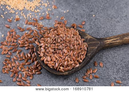 healthy flaxseeds in wooden spoon on stone textured background.