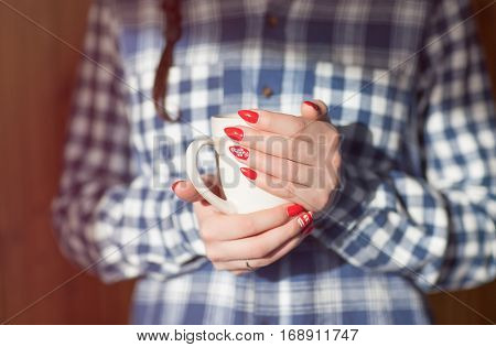Young woman with winter nordic print style red nails warming hands up by hot coffee cup