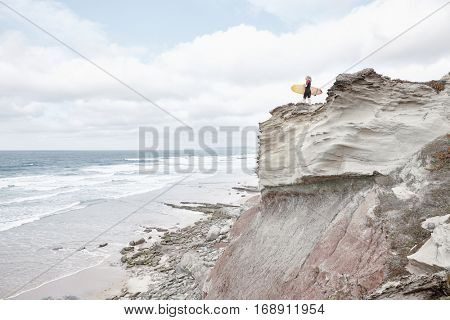 Young blonde woman wearing shorty wetsuit, standing on edge of cliff with surfboard in her hands, reading waves and preparing for surfing session - water sports concept. Baleal, Peniche, Portugal