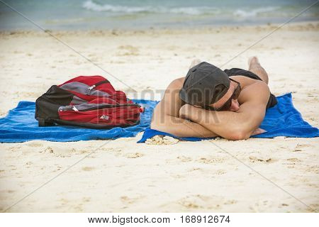 Portrait of a man in a cap and sunglasses sunbathing on the beach on towel, next to backpack