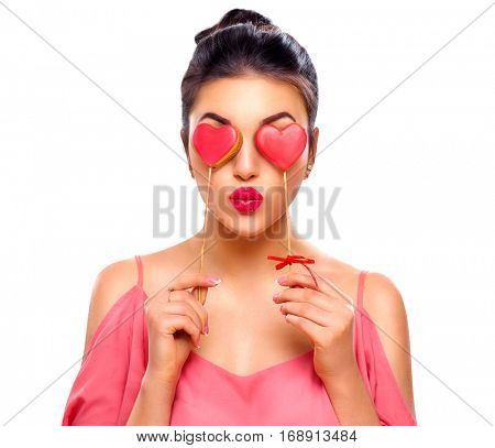 Beauty joyful Young fashion model Girl with Valentine Heart shaped cookies in her hands. Love Concept. Beautiful smiling young woman. Valentines Day gift. Isolated on white background.