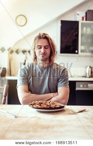 Young man sitting in his kitchen is unhappy with a burnt pizza for lunch.