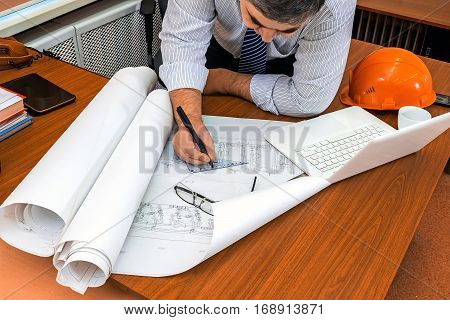 Disigner at work. Checking the project. Correction of the drawing.