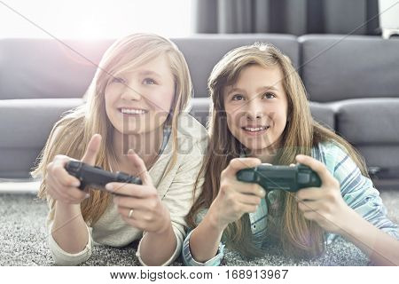 Sisters playing video games in living room