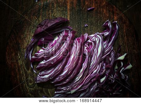 Finely chopped red cabbage on grunge wooden chopping board. View from above.