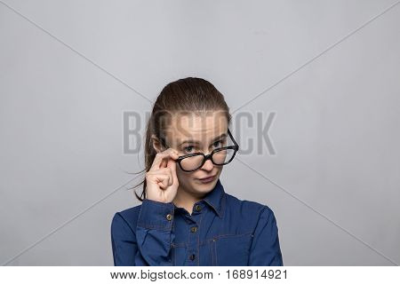 Portrait of grumpy woman in glasses on gray background