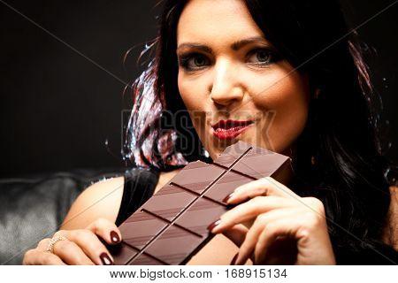 Studio shot on black background of a young woman enjoying chocolate