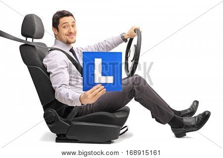 Guy sitting on a car seat and holding an L-sign isolated on white background