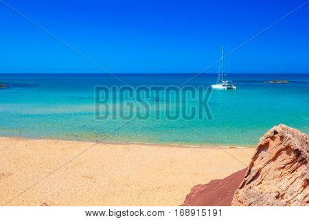 Cala del Pilar beach scenery with white yacht on sunny summer day at Menorca, Balearic Islands, Spain.