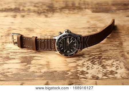 Stylish watch with leather wristlet on wooden background