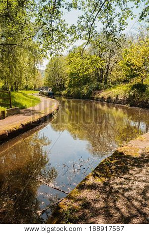 Shady tree lined view of the Llangollen canal with a narrowboat tied up on the bank a beautiful part of the British inland waterway network