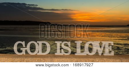 3D words saying 'God is love' as the sun goes down into clouds over a river lagoon.