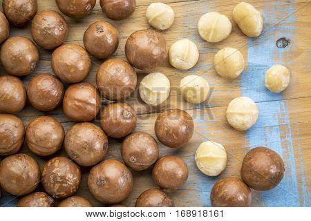 macadamia nuts in shells and without on a rustic grunge wood - top view