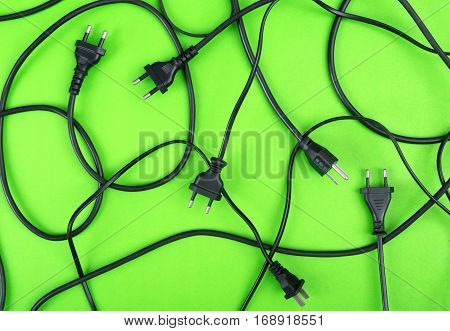 Messy of electrical cords plug and wires unconnected top view on colorful background messy electric equipment flat lay concept.