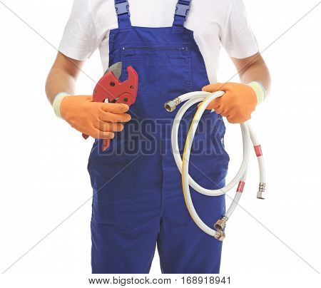 Young handsome plumber with cutter and flexible hose on white background