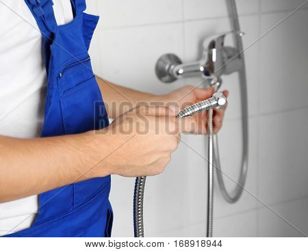 Young handsome plumber fixing shower, closeup