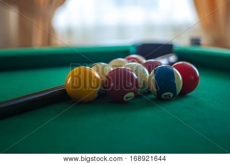 Billiard Balls On Green Table With Billiard Cue In A Hotel Hall