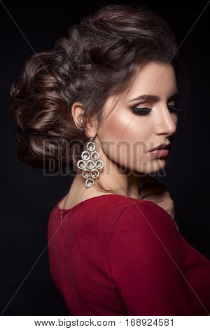 Beautiful woman with stylish haircut and big earrings looking down over shoulder touching neck by hand. Brunette girl posing in dark studio wearing red dress with evening make up and long eyelashes