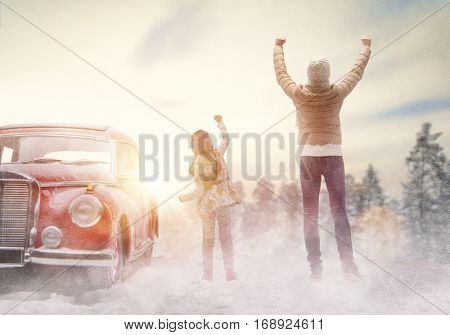 Toward adventure! Happy family are relaxing and enjoying road trip. Mother, child and vintage car on snowy winter nature background. Christmas holidays time.