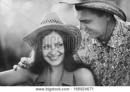Monochrome portrait of young couple in hats sitting on ground smiling and touching each other. Wife and husband having fun and touching each other. Walking outdoors together in summertime.