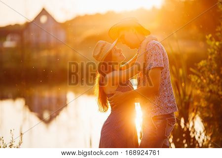 Happy couple of brunette girlfriend in dress and boyfriend in shirt and hat embracing on pier of lake at sunset in warm sunny day. Lovers smiling and looking each other. Romantic atmosphere.