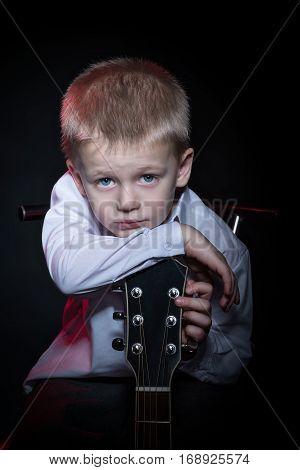 Portrait of a little boy in a shirt, leaning on guitar fingerboard
