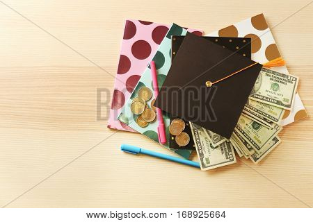 School supplies, graduation hat, banknotes and coins on wooden table. Pocket money concept
