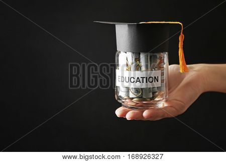 Female hand holding glass jar with money for education, on dark background