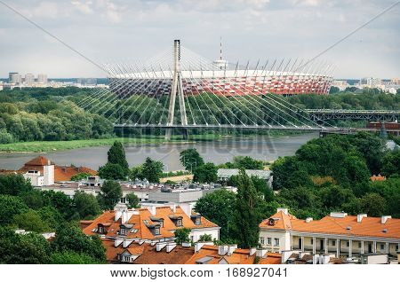 Cityscape of Warsaw. Old architecture with red roofs on the foreground Holy Cross Bridge Swietokrzyski Bridge over the Vistula river National Stadium Stadion Narodowy Poland