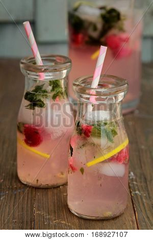 Bottles of pink lemonade with raspberry and mint standing on a wood background