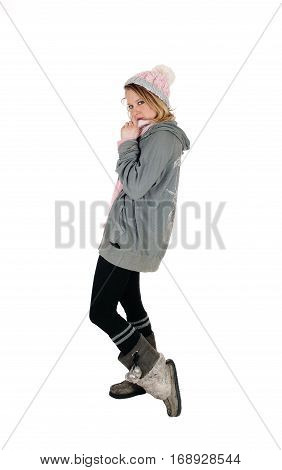 A lovely young woman standing in profile with a knitted hat tights and boots isolated for white background.