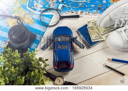 Travel - concept. Traveler's accessories Essential vacation items camera touristic maps on the white desk. Travel background. Car journey planning. Tourist essentials. Space for text