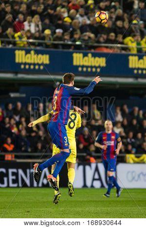 VILLARREAL, SPAIN - JANUARY 8: 3 Pique, 8 Dos Santos during La Liga soccer match between Villarreal CF and FC Barcelona at Estadio de la Ceramica on January 8, 2016 in Villarreal, Spain