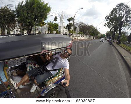 Man taking a selfie on Tuk Tuk in Bangkok, Thailand